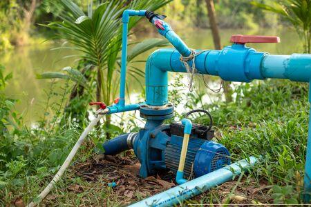 ฺBlue Water pump on the ground near the water.