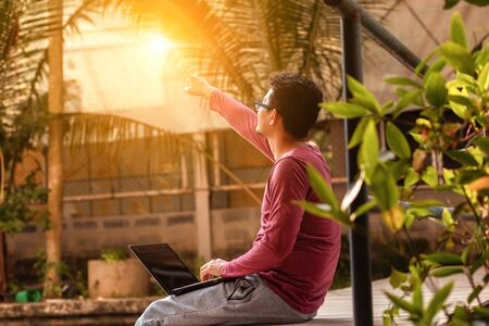 man working on laptop while sitting on wooden dock. legs in river water and hand pointing out in sky at sunset.