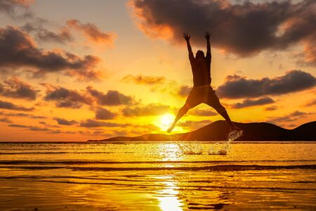 Happy man jumping on the beach and water splash. Mountain, sea water and beautiful cloud is landscape.