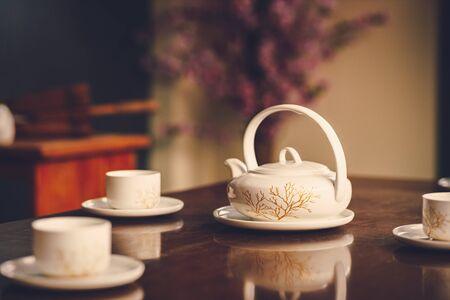 Teapot on the table near cup of tea.