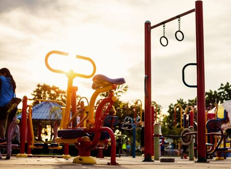 Colorful exercise equipment in public park and sunset.