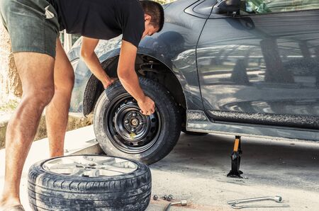 Change a flat car tire at car park with Tire maintenance, damaged car tyre Фото со стока