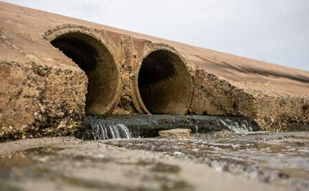 Dirty water stems from the pipe polluting the sea. The danger for the environment.