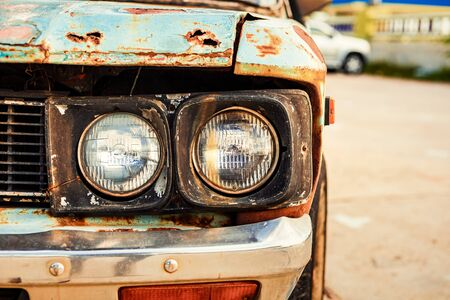 headlights of old car with cracked and peeling paint at park.