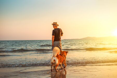 A man and a dog stand on the beach and sunset.