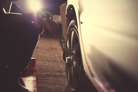 Change a flat car tire  with Tire maintenance, damaged car tyre at night. Фото со стока