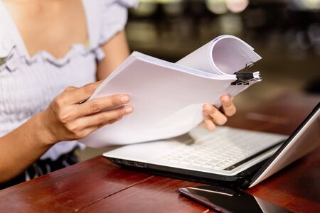 woman opening and reading a paper sheet near laptop on wooden table.