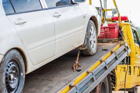 Kette binden Autorad am Abschleppwagen im Park. Schaden und Unfall Auto.