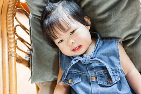 Cute baby girl lie down on pillow. Children happy and funny. Фото со стока