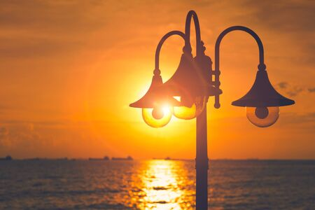 Lamp post near the sea and light of sun with lens flare.
