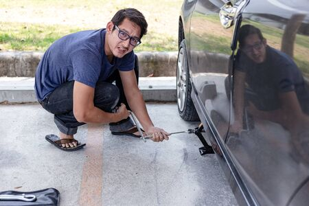 Hands using hydraulic jack - car maintenance concept. Car tire changed for maintenance in garage Фото со стока
