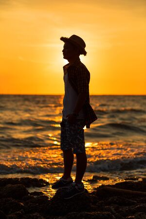 A man stand on the stone near the beach. A travel man wear hat and sunset.
