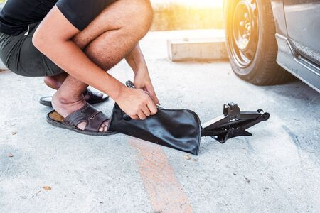Car tire changed for maintenance in garage using hydraulic jack, car maintenance concept