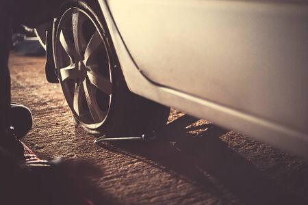 flat car tire  with Tire maintenance, damaged car tyre at night.