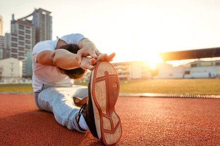Full length portrait of a athletic man stretching at sport stadium and sunset.