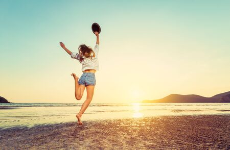 travel women hold hat and jump on the sea wave and sunset. Фото со стока