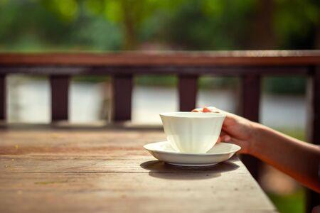 A women hand hold cup of tea on wood table. Tea time. Фото со стока