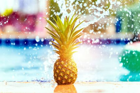 pineapple with water splash near the pool.