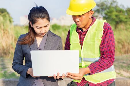 Businesswomen and foreman talking together. Engineer and manager teamwork and checking at site construction .