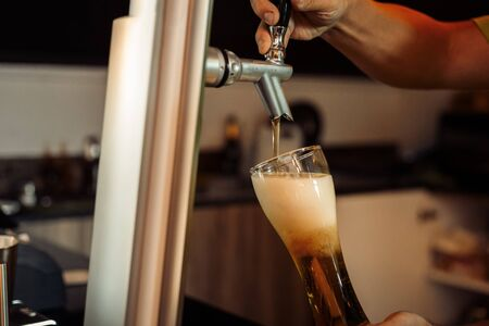 bartender hand pouring a large lager beer in tap.