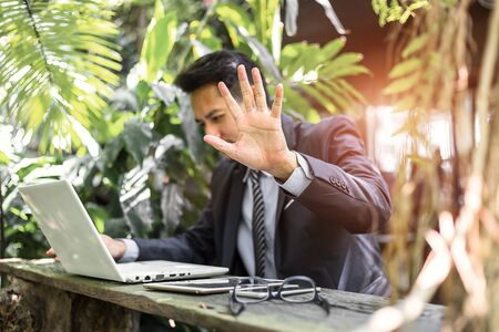 Hand stop shown by businessman between working on laptop.