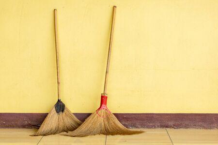broom on the ground near yellow wall.