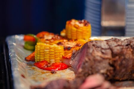Pork ribs with corn on a board. American food at to hotel restaurant.