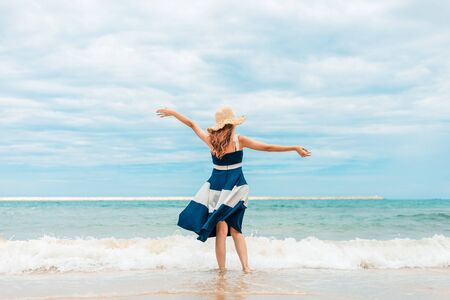 Femme heureuse en vacances d'été portant un chapeau et une robe en profitant de la vue sur la plage de l'île.