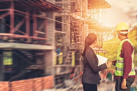 Businesswomen and foreman shake hands together. Engineer and manager teamwork and checking at site construction .