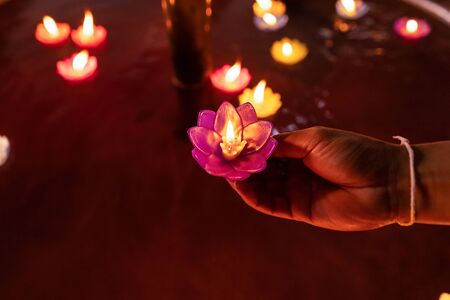 Hands of Buddhist floating colorful Candle floating on water for pray buddha at night.