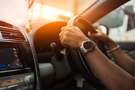 hand man wear watch and drive a car