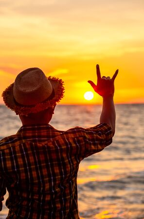 hands forming a love sign with sunset on the beach with sunset. Фото со стока