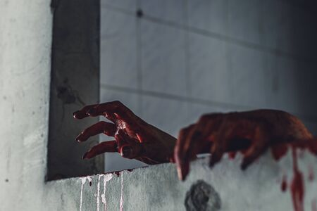 horror scene of woman with scary hand  at abandoned house. hand through the hole wall. Halloween concept Imagens
