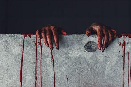 Horrorszene einer Frau mit gruseliger Hand im verlassenen Haus. Hand durch die Lochwand. Halloween-Konzept