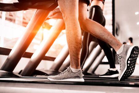 Cierre de pie Fitness hombre corriendo en cinta de pista, ejercicio físico.