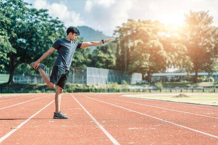 Full length portrait of a athletic man stretching at sport stadium. Фото со стока - 146855407