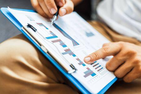 ビジネスマンはペンを保持し、作業計算データ。ドキュメントグラフチャートとレポートマーケティング事業所のコンセプト。