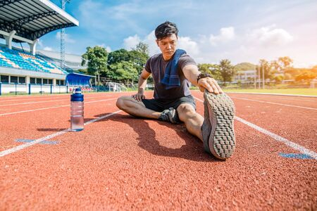 Full length portrait of a athletic man stretching at sport stadium.