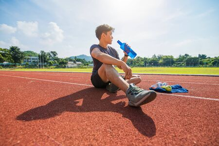 Sport man sitting and holding water bottle on track race at sport stadium in the morning. enjoy and lifestyle concept. Фото со стока - 146852658