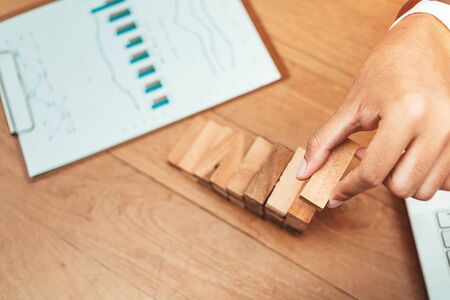 Male hand stacking wooden blocks. Business development and growth concept