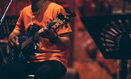 Mano de hombre tocando la guitarra acústica y cantando en el escenario por la noche.