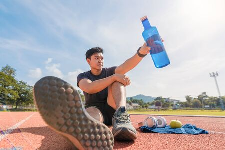 Sport man sitting and holding water bottle  on track race near green apple and music headphone on towelat sport stadium in the morning. Sport, workout and lifestyle concept. Фото со стока
