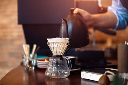 barista pouring boiling water from kettle to drip coffee maker.