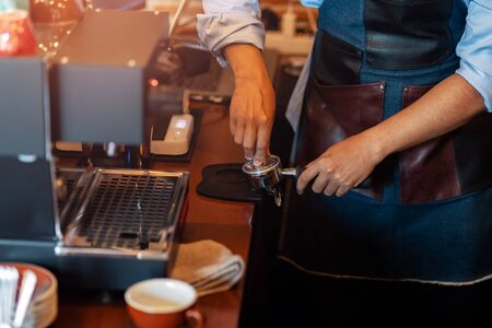 Barista holding portafilter and coffee tamper making coffee at cafe.