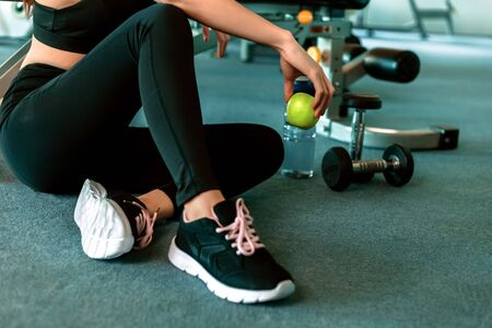 Woman exercise in gym fitness breaking and relax. hand  holding apple fruit after training sport and dumbbell, water bottle on the ground.