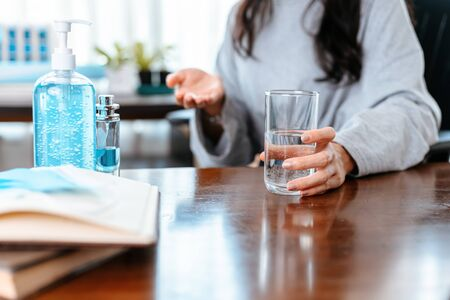 Businesswomen working at home with glass of water takes white round pill in hand. Фото со стока