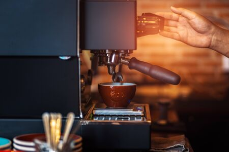 Barista making fresh coffee with coffee machine in cafe