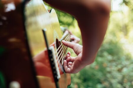 woman's hands playing acoustic guitar have fun outdoor, close up. Reklamní fotografie