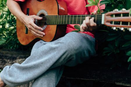man's hands playing acoustic guitar have fun outdoor, close up.