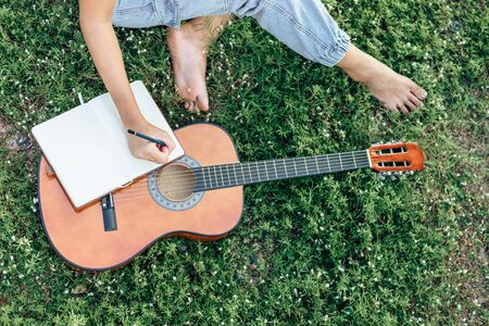 songwriter create and writing notes,lyrics in the book on grass at parks.